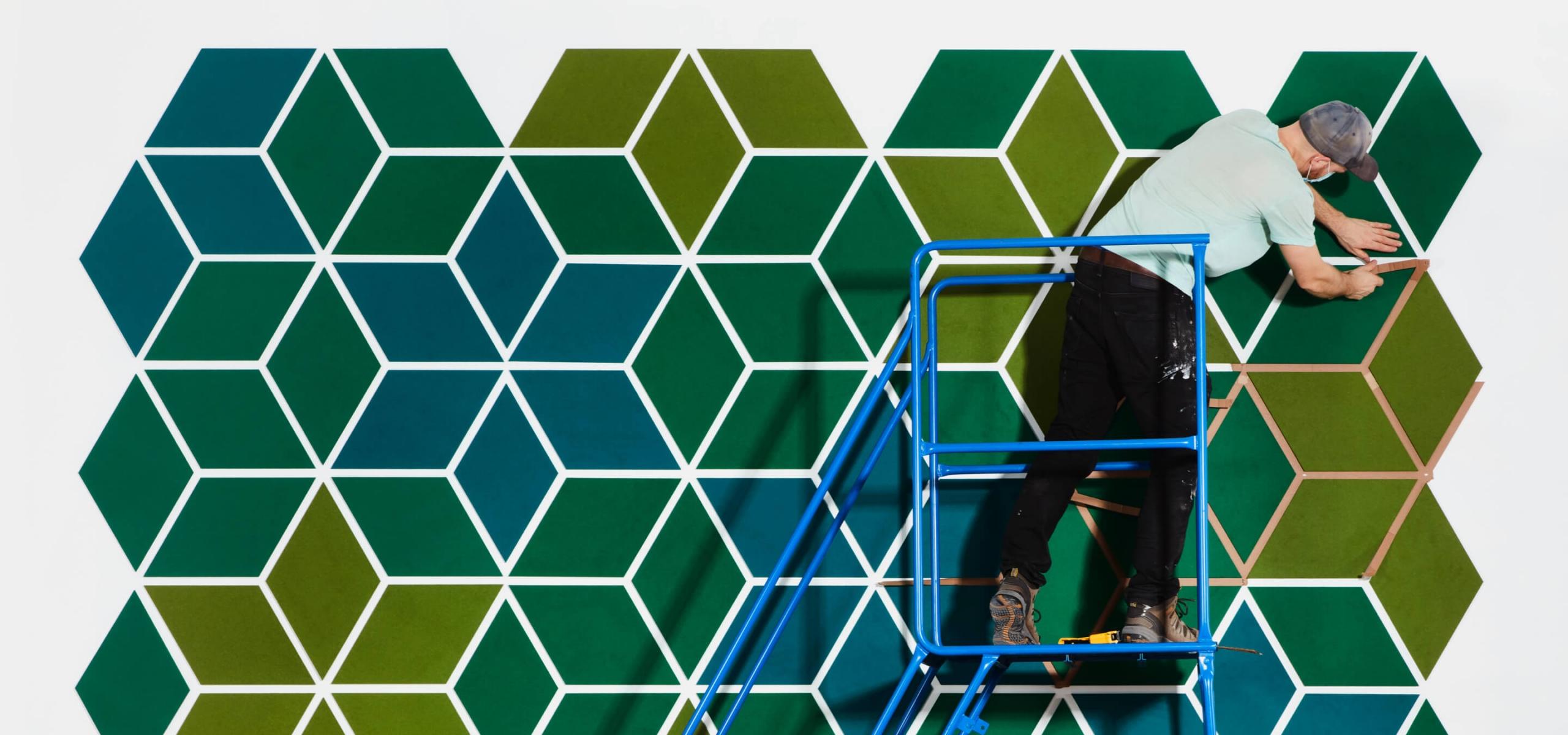 Man installing tiles of diamond shaped felt on wall